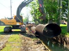 A large dirt-mover lifting a storm drain out of the ground